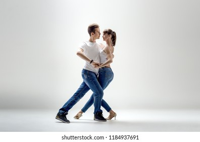 beauty couple dancing social danse ( kizomba or bachata or semba or taraxia) , on light-grey background