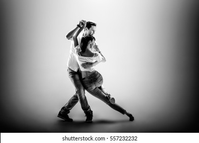 Beauty couple dancing social danse ( kizomba or bachata or semba or taraxia) , on grey background. Black-and-white photo