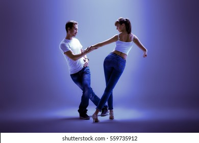 beauty couple dancing social danse ( kizomba or bachata or semba or taraxia) , on blue background, blue, violet tone