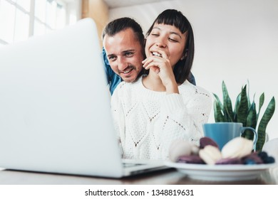 Beauty couple spending time at home together. Bright spacious apartment, cookies and drinks and watching laptop with surprise