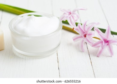beauty cream and pink hyacinth on white wooden