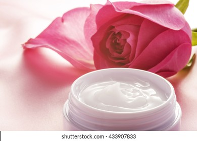 Beauty cream and rose on pink cloth