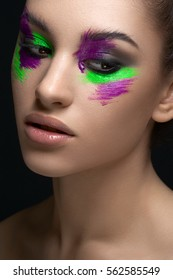 Beauty and creative make-up theme: beautiful young woman model with creative makeup green-purple paint on his face in the studio