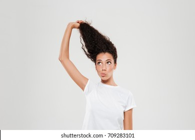 Beauty curly woman pulling up her hair over gray background