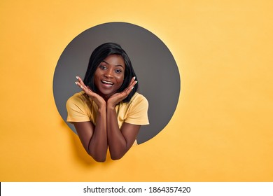 Beauty cute portrait of young african american woman. Woman posing in a circle hole in yellow background, looking at camera, smiling. Studio shot. Copy space.