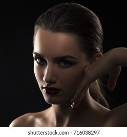 Beauty dark portrait of young model girl face hold hand near cheek. Dark glossy lips make-up, clean skin. Silhouette style. Black background