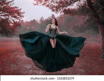Beauty dark queen in black fantasy creative dress levitates in air. Sexy warrior corset design, bare long legs. Backdrop autumn forest red trees. fabric skirt waving fluttering in wind. Fashion style