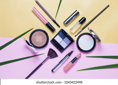 Beauty, decorative cosmetics. Makeup brushes set and color eyeshadow palette on pink and blue background , flat lay, top view, Minimalistic style.