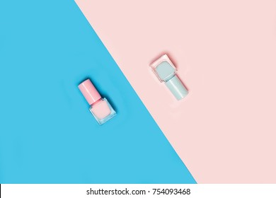 Beauty, decorative cosmetics. Makeup set and color nail polish on pink and blue background , flat lay, top view.