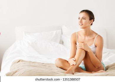 beauty, depilation, epilation and bodycare concept - beautiful woman touching her bare legs sitting on bed at home bedroom
