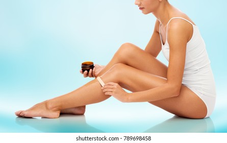 beauty, depilation, epilation, hair removal and people concept - beautiful woman with applicator applying depilatory wax to her leg over blue background