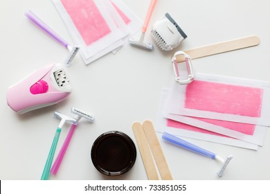 beauty, depilation and hair removal concept - wax with spatula, epilator and safety razor on white background