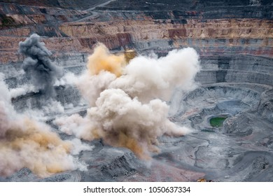 Beauty of destruction: Aerial view to open mine after explosion, featuring colorful smoke and dust polls