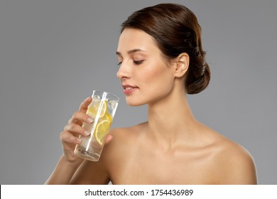 beauty and detox concept - woman drinking fresh water with lemon and ice over grey background