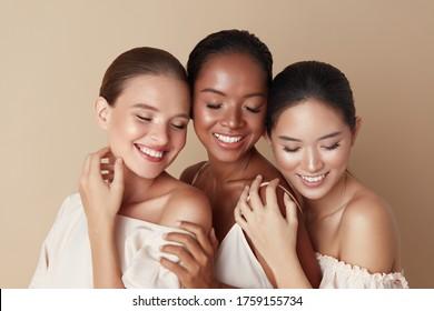 Schönheit. Verschiedene Gruppen von ethnischen Frauen Porträt. Fröhliche verschiedene Ethnizitätsmodelle, die zusammen mit geschlossenen Augen und Lächeln stehen. Herrliche, multiethnische Mädchen mit Nude auf beigem Hintergrund.