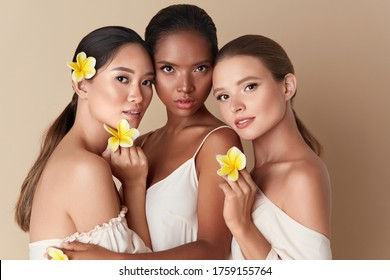 Beauty. Diverse Group Of Women Portrait. Tender Models Of Different Ethnicity Posing With Tropical Flowers In Hands. Asian, Mixed Race And Caucasian Female With Healthy Skin Holding Plumeria.