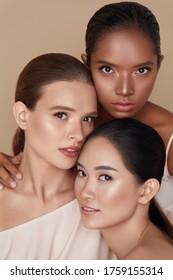 Schönheit. Diverse Models Porträt. Bieten Sie Frauen mit kaukasischem, asiatischem und gemischtes Rennen auf beigem Hintergrund an. Weibliche mit perfekter Haut und natürlicher Schminke, die Kamera anschauen.