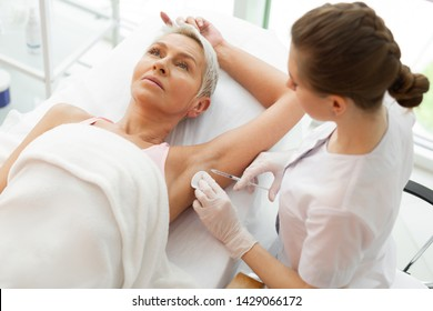 Beauty doctor. Professional female cosmetologist holding a syringe while doing the underarm injection