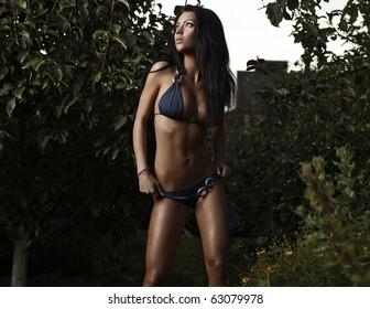 beauty dressed bikini poses in an autumn garden of apples.