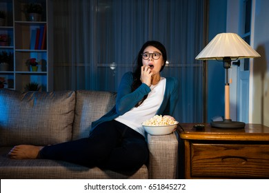 beauty elegant girl watching horror movie at night looking at terrible plot feeling fearful and shocked with sitting in living room sofa eating popcorn.