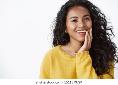Beauty, emotions and women concept. Attractive african american woman with no flaws, blemishes, touching pure clean skin and smiling with delight, feeling happiness, gazing camera tenderly