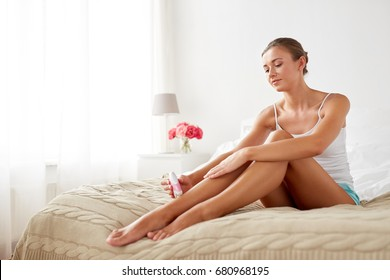 beauty, epilation and bodycare concept - beautiful woman with epilator removing hair from legs sitting on bed at home bedroom