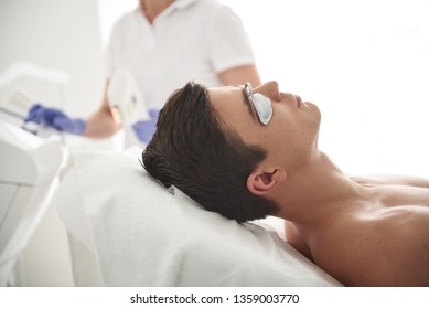Beauty esthetics treatment. Close up side on portrait young naked man in cosmetic center waiting while female specialist adjusting devise for IPL hair removal