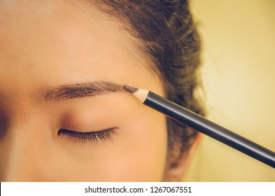 Beauty face of Asian woman by applying eyebrow pencil, The girl is makeup her face with eyebrow pencil, Soft and smooth face skin by cosmetics and foundation and using makeup brush on the face.