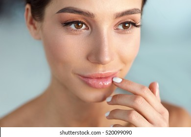 Beauty Face. Beautiful Woman With Natural Makeup And Sexy Full Lips Touching Her Mouth. Closeup Portrait Of Smiling Model Girl With Healthy Smooth Facial Skin Applying Lip Balm On Lip. High Resolution