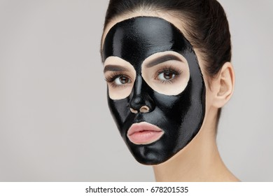 Beauty Face Black Mask. Closeup Of Young Female With Natural Makeup And Black Peel Off Mask On Skin. Portrait Of Attractive Woman With Cosmetic Peeling Product On Beautiful Face. High Resolution