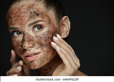 Beauty Face Care. Portrait Of Attractive Young Woman Putting Coffee Scrub On Facial Skin. Closeup Beautiful Sexy Female Model Touching Face With Hands, Exfoliating And Scrubbing Skin. High Resolution