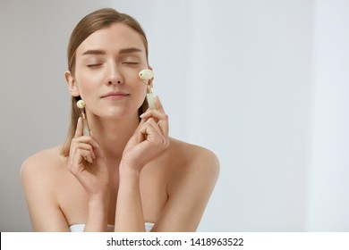 Beauty face care. Woman doing face massage with jade facial rollers for spa skin care treatment at home. Girl using natural massager tool portrait on light background
