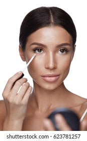 Beauty Face. Closeup Of Sexy Young Woman With Concealer Brush And Mirror In Hands. Portrait Of Beautiful Healthy Female Model Applying Concealer Under Eyes. Skin Cosmetics. High Resolution