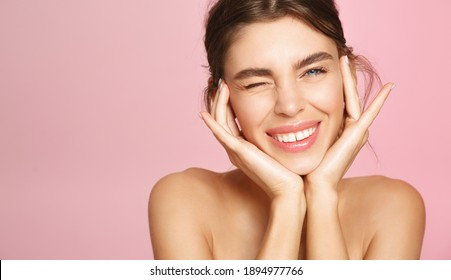 Beauty face. Happy young woman getting ready for romantic valentines day date, applying makeup and smiling. Pretty girl standing naked, nourish and hydrate skin on pink background.