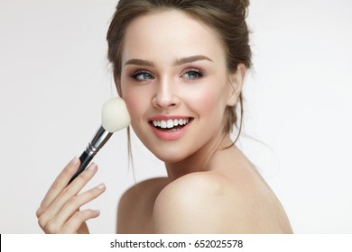 Beauty Face. Portrait Of Beautiful Smiling Girl Applying Loose Blush With Cosmetic Brush. Closeup Of Beautiful Young Woman With Soft Smooth Skin And Fresh Makeup. Skin Cosmetics. High Resolution
