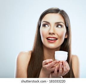 Beauty face portrait. Smiling woman. Young model hold skin care cream. Isolated.