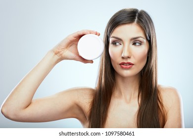 Beauty face portrait of young woman with long hair holding skin care cream. Isolated close up face portrait.