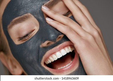 Beauty face skin care. Woman with cosmetic spa facial mask. Smiling girl model with grey clay mask and beautiful white smile closeup portrait