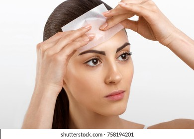 Beauty Face. Skin Care. Woman removing oil from face using blotting papers. Closeup Portrait Of Beautiful Healthy Girl With Nude Makeup. Perfect Soft Skin With Oil Absorbing Tissue Sheets.