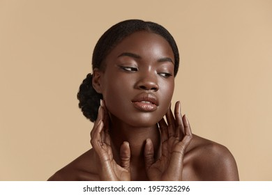 Beauty face. Smiling black woman touching healthy skin portrait. Beautiful girl with glowing skin and natural makeup`. Skin care concept