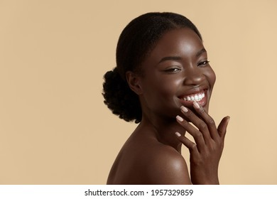 Beauty face. Smiling black woman touching healthy skin portrait. Beautiful girl with fresh glowing hydrated facial skin and natural makeup on blue background at studio. Skin care concept