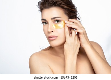 Beauty face woman with a healthy flawless skin applying eye patch. Woman with bare shoulders and her long brown hair tied back applying a hydrogel eye patch in a beauty treatment concept over white