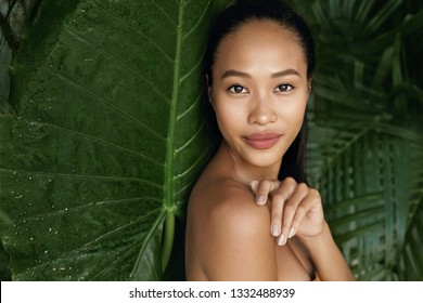 Beauty face. Woman model with natural makeup and healthy skin in tropical nature. Beautiful asian girl portrait with jungle leaves on background