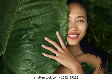 Beauty face. Woman model with natural makeup and healthy skin behind green leaf plant. Portrait of beautiful asian girl with nude nails, big lips and sexy smile in tropical nature