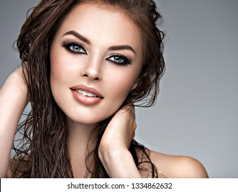 Beauty face of the young beautiful woman. Gorgeous female portrait with slicked brown hair. Young adult smiling girl with healthy skin. Pretty model with fashion smokey eye makeup. Skin care concept.