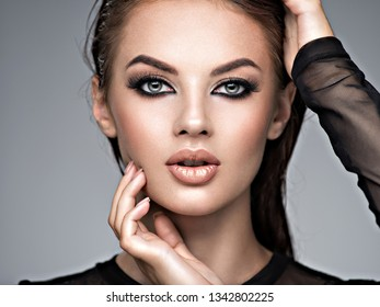 Beauty face of the young beautiful woman. Gorgeous female portrait with slicked brown hair. Young adult girl with healthy skin. Pretty model with fashion smokey eye makeup. Skin care concept.