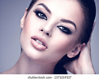 Beauty face of the young beautiful woman. Gorgeous female portrait with slicked brown hair. Pretty model with fashion smokey eye makeup. Professional makeup