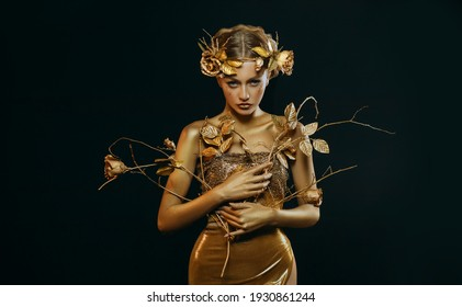 Beauty fantasy woman, face in gold paint. Golden shiny skin. Fashion model girl, image goddess. Glamorous crown, wreath roses, jewellery accessories. Professional metallic makeup. hand holds a branch