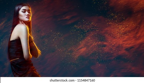 Beauty, fashion. Beautiful woman in black dress with sparks in dark