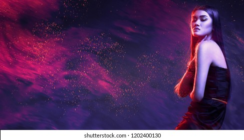 Beauty, fashion. Beautiful woman in black dress with red sparks in dark